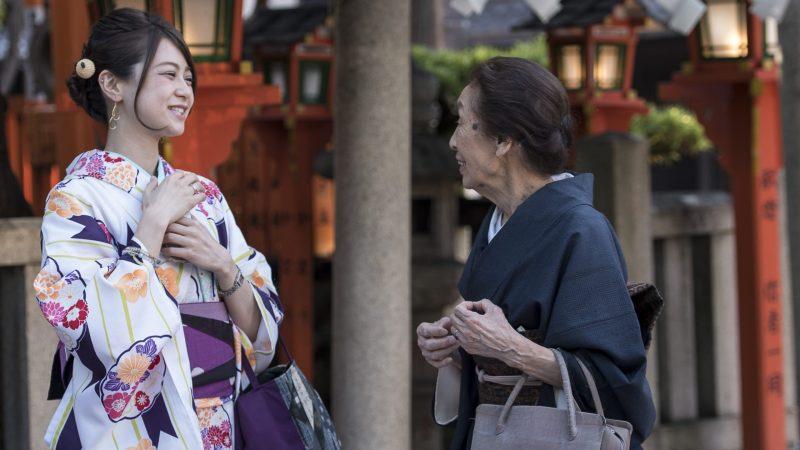 Begegnung in Japan: Zwei in traditionelle Kimonos gekleidete Frauen unterhalten sich bei der Gion Tatsumi Brücke.