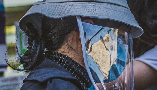 Mulher com chapéu, máscara e protetor facial de perfil, caminhando.