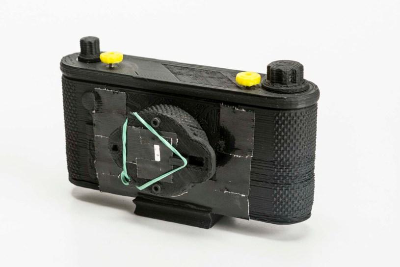 Cámara impressa en 3D con disparador de goma de pollo. Formato: 35mm