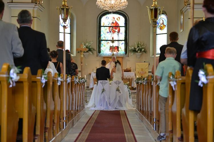 Para młoda podczas ceremonii ślubnej na tle ołtarza