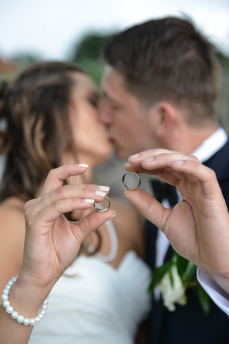 Pocałunek pary młodej na tle trzymanych w rękach obrączek