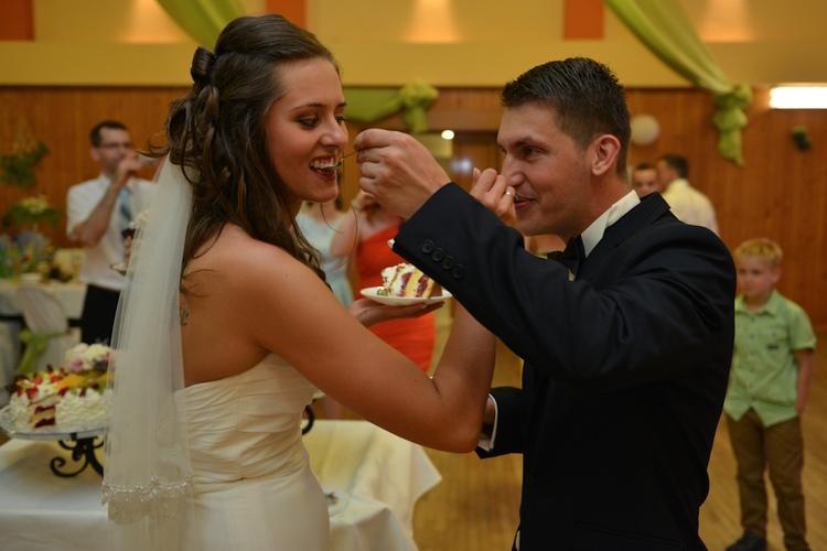 Para młoda z Pszczyny dzieli się tortem weselnym
