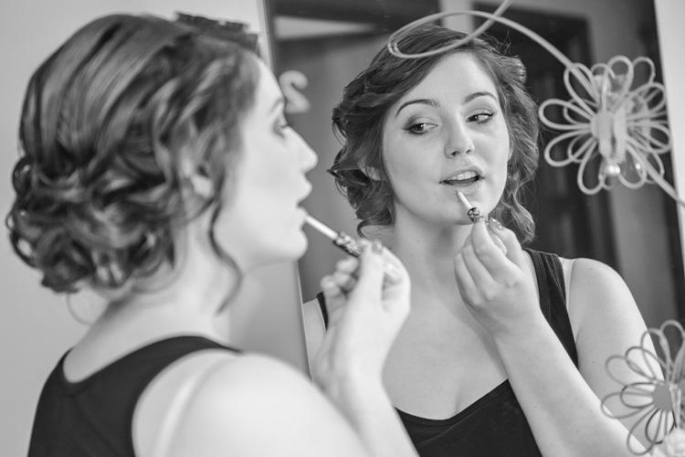 Panna młoda poprawia makijaż przed lustrem.