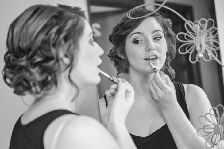 Panna młoda poprawia makijaż przedlustrem.