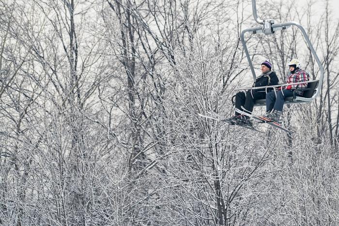 Narciarze nawyciągu natle ośnieżonych drzew