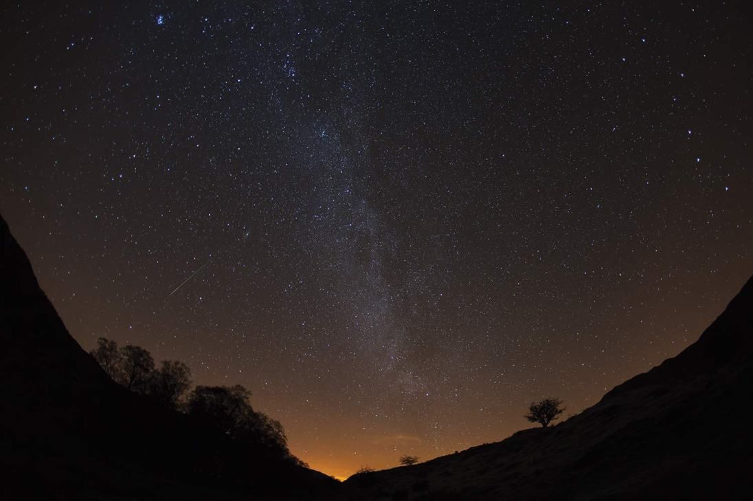 The Thirlmere Valley is the best place I have found locally to avoid too much light pollution. The lights of Keswick still give a yellow glow on the horizon. A bright Geminid meteor is caught during this 40 second exposure. Canon 5D MkII, 15mm Fisheye corrected, ISO 1600, 40 sec at f/2.8, tripod. © Stuart Holmes 2014