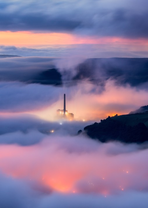 Pre-dawn mist and lights looking down on the village of Castletown and the Hop Cement Works, Peak District.
