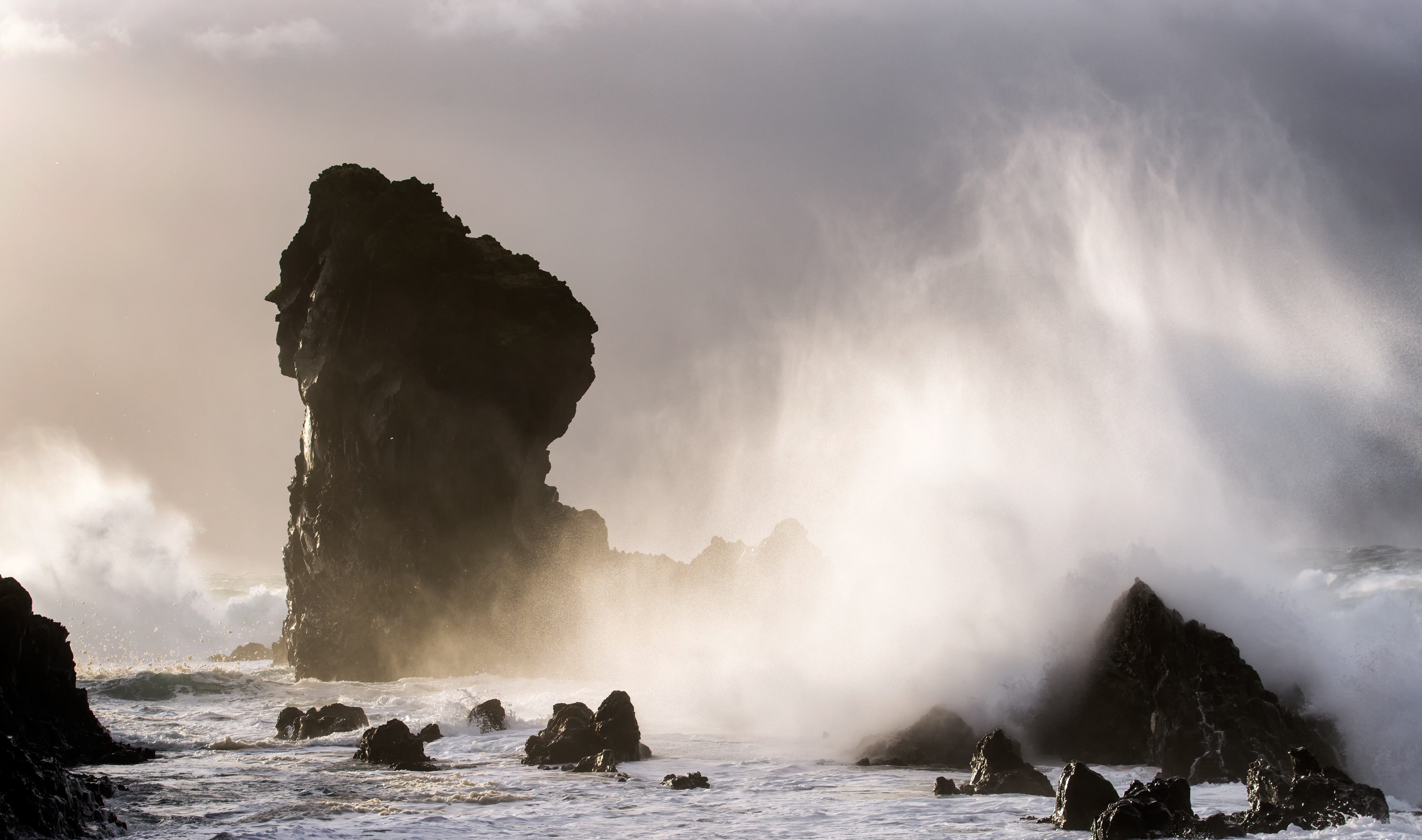Crashing waves cover a sea stack in Iceland.