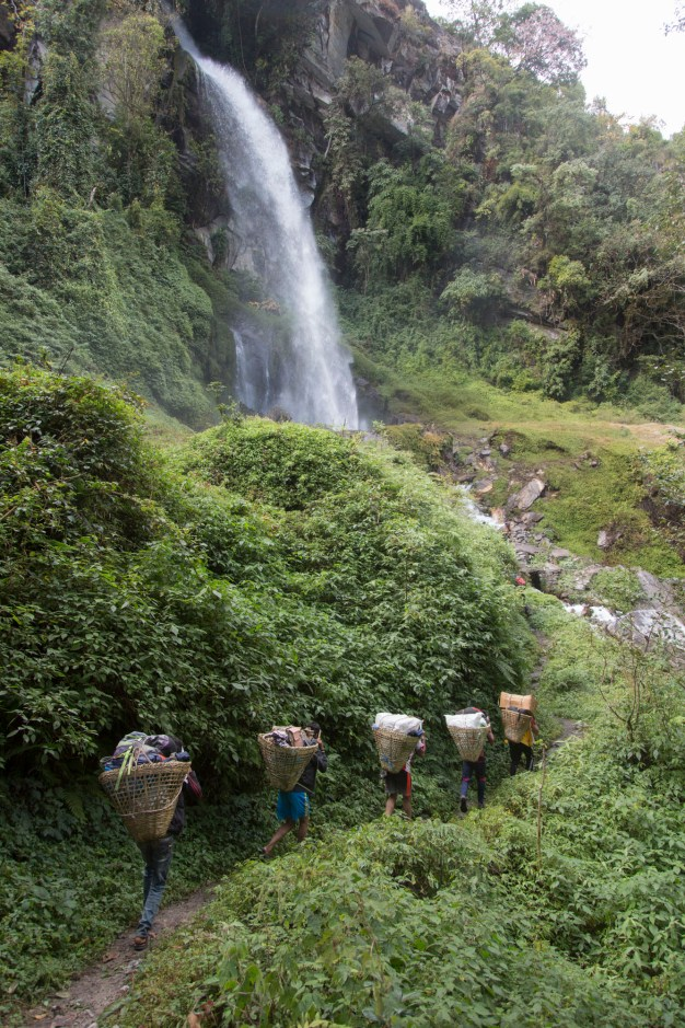 Some of our porters passing below one of many waterfalls. Canon 5D MkIII, 24-105mm at 24mm, ISO 400, 1/200 sec at f/4, © Stuart Holmes.