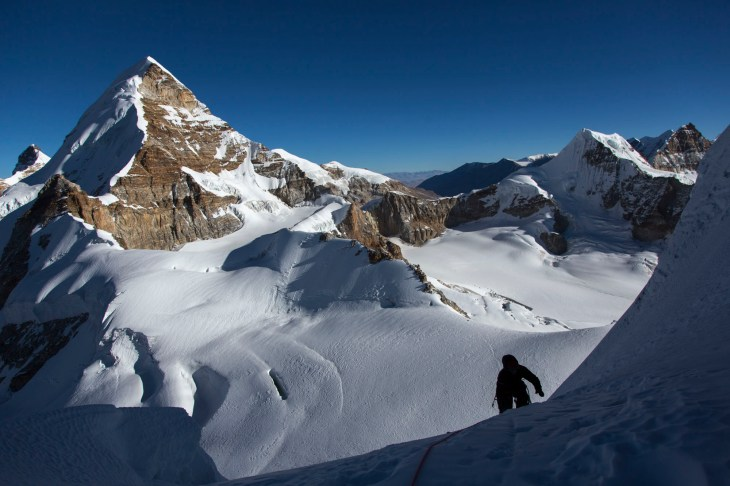 Lucy climbs up towards our high point with Nangmari I (6500m) behind. Canon 5D MkIII, 24-105mm at 24mm, ISO 100, 1/1000 sec at f/7.1. © Stuart Holmes.