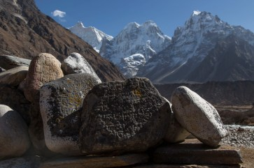 Buddhist carved mani stones with the impressive north face of Jannu behind. Canon 5D MkIII, 24-105mm at 32mm, ISO 100, 1/500 sec at f/6.3. © Stuart Holmes.