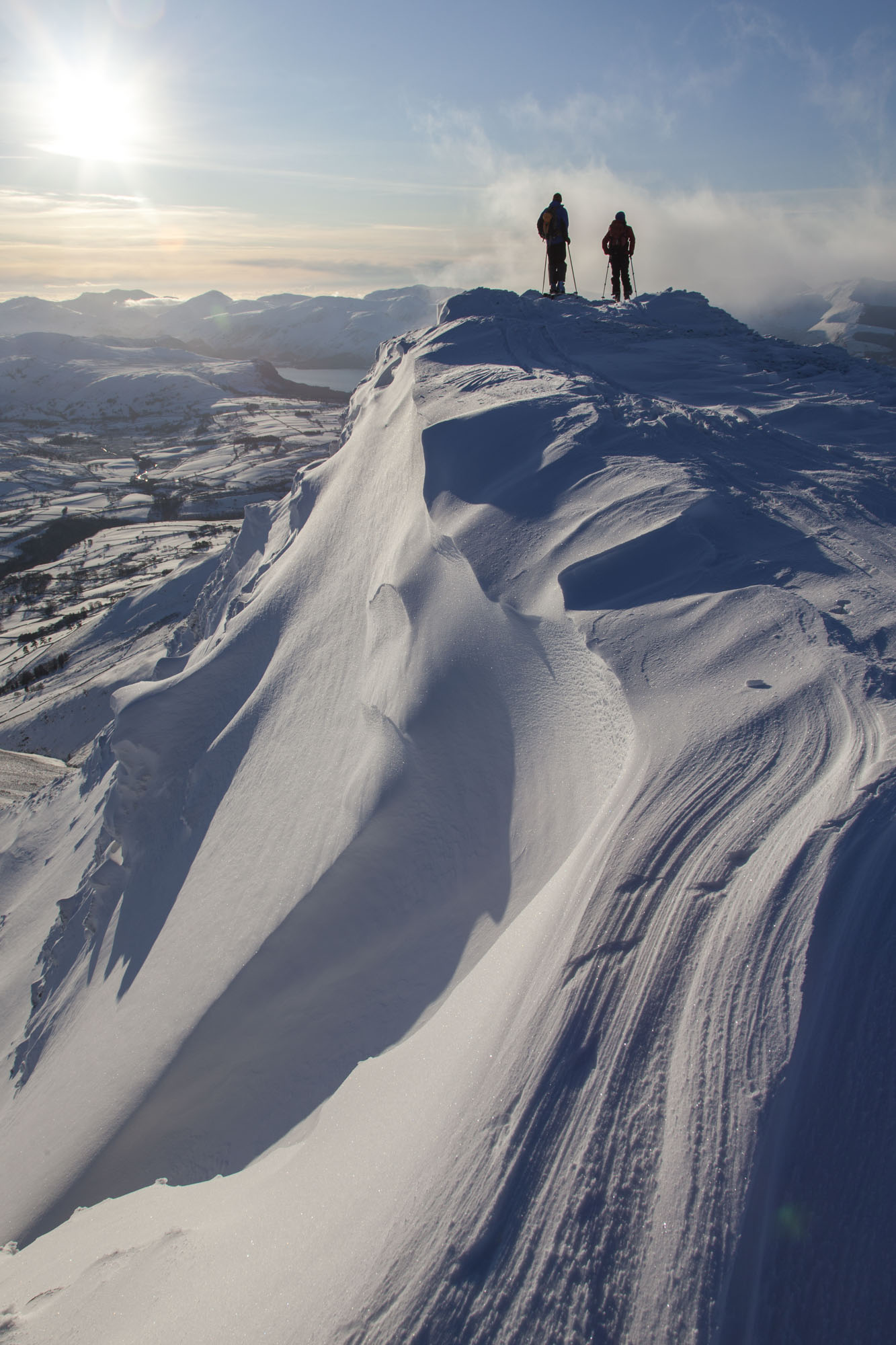 Wind sculpted snow is called sastrugi. Skiers taking in the view on top of Blencathra. Canon 5D MkII, 24-105mm at 24mm, ISO 100, 1/320 sec at f/13, December. © Stuart Holmes.