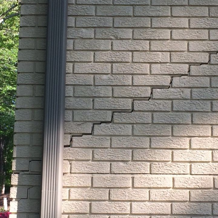 exterior stair step crack on white wall