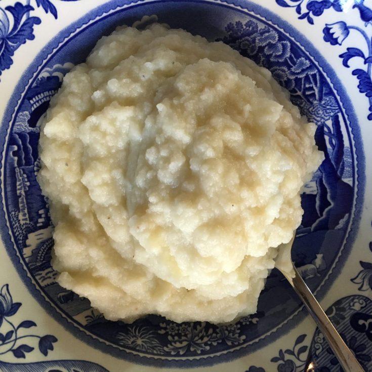 mashed cauliflower in blue white porcelain serving bowl