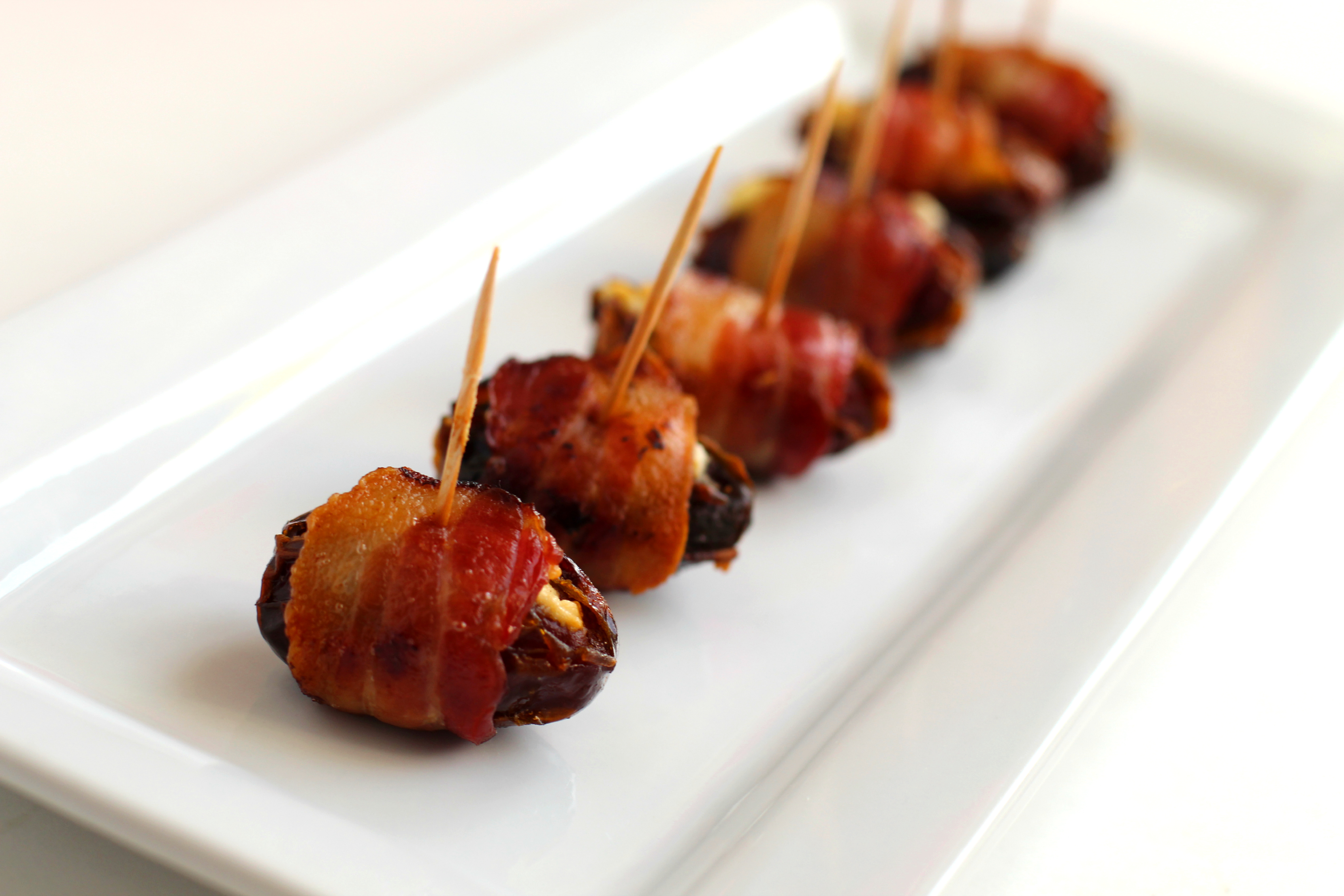 Bacon wrapped dates with goat cheese on a plate