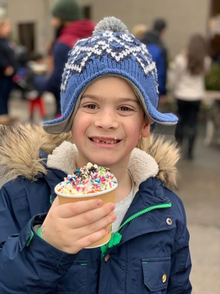 boy with hat smiling with a hot chocolate