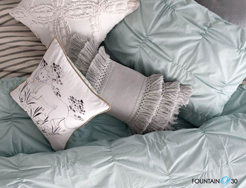 How To Use Textiles In Your Home grey blue pillows on bed