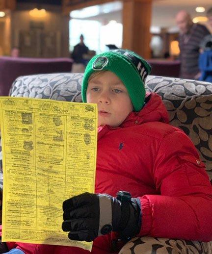 Boy reading a piece of paper in winter gear