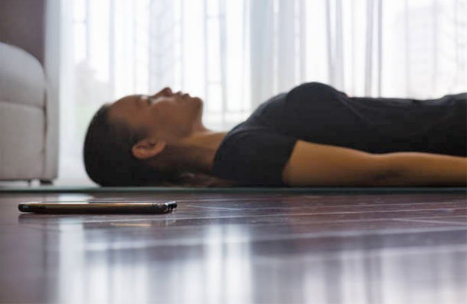 meditation woman on floor with phone app Fitness Beyond The Gy foubntainof30