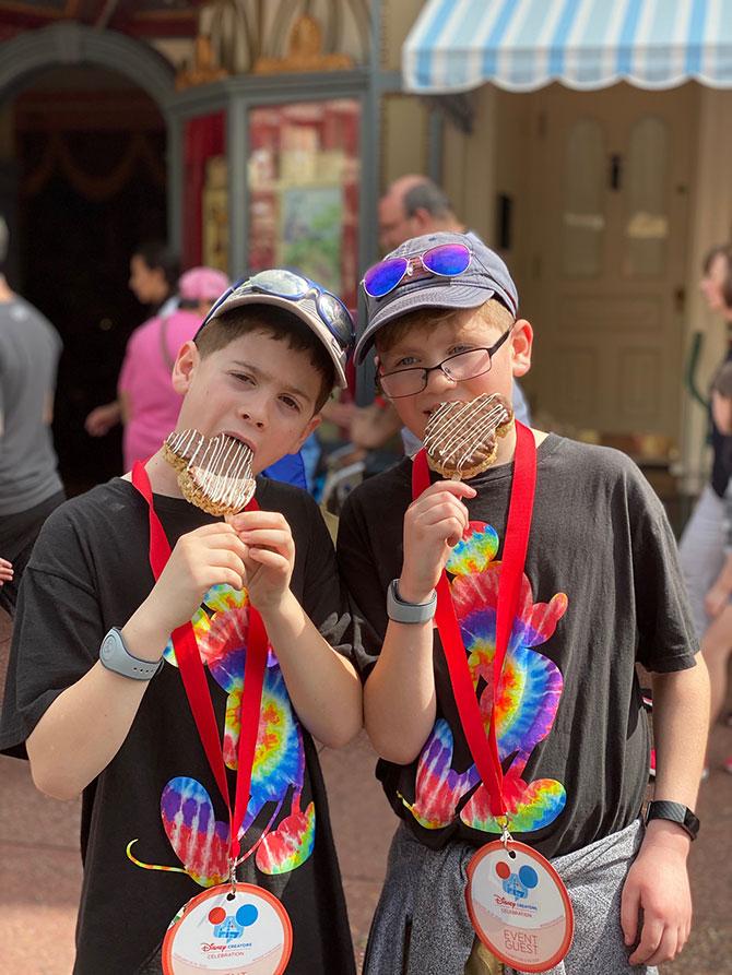 two boys at disney world magic kingdom eating rice krispie treats fountainof30