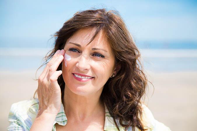 woman applying sunscreen to face fountainof30