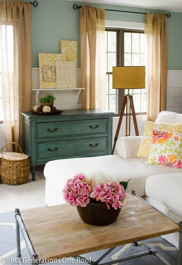 Burlap curtains in a modern farmhouse living room, white sectional, green buffet, blue walls, shiplap white walls, pink hydrangeas, wood and iron coffee table, tripod floor lamp