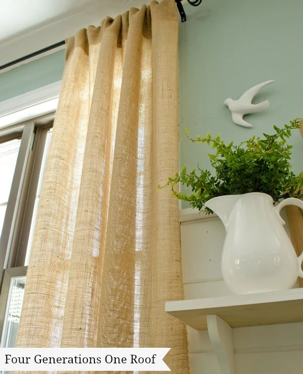 Burlap curtains, black curtain rod, in a modern farmhouse living room, blue walls, shiplap white walls, flying dove on wall, white pitcher with greens, white wood shelf