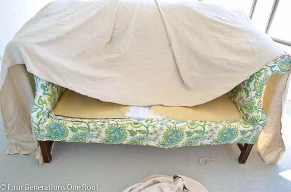 pottery barn white slipcover used to reupholster a couch , cement floor, pool house