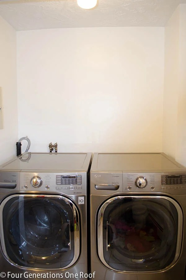 white laundry closet with side by side stainless steel LG washer dryer