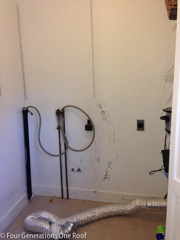 ugly white laundry closet with pipes