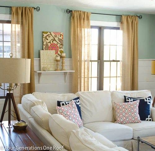 diy burlap curtains, seashells sign, wood candle holders, diy flower fabric wall art, whythe blue paint, white shiplap, white sectional, blue and white pillows , tripod table lamp, white diy shelf