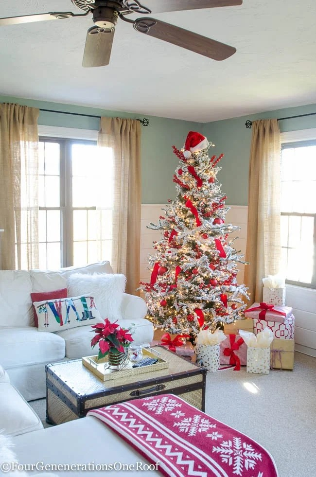 Burlap curtains, white shiplap walls, blue wall paint, white sectional, red and white Christmas tree, brown wicker coffee table storage trunk, red poinsettia, red nordic throw blanket, santa hat, christmas gifts