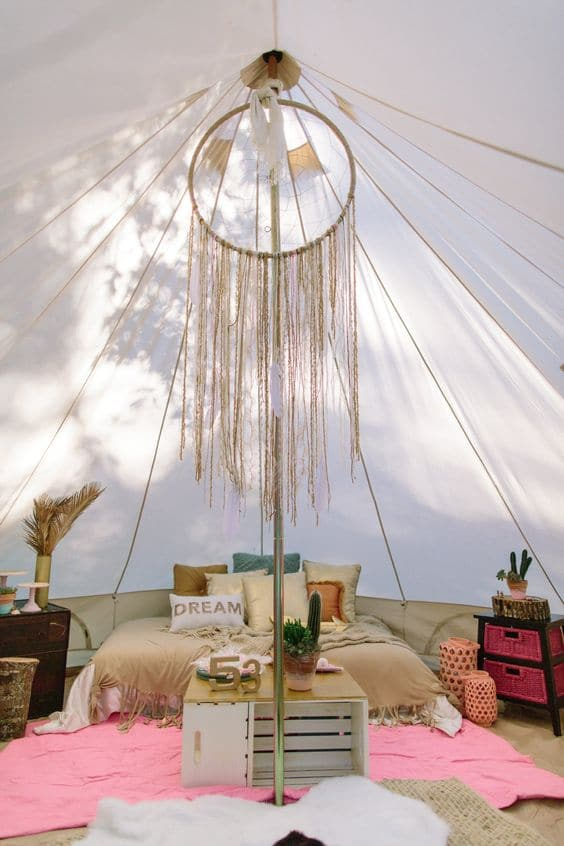 boho style white tent for camping with pink rug and queen size bed