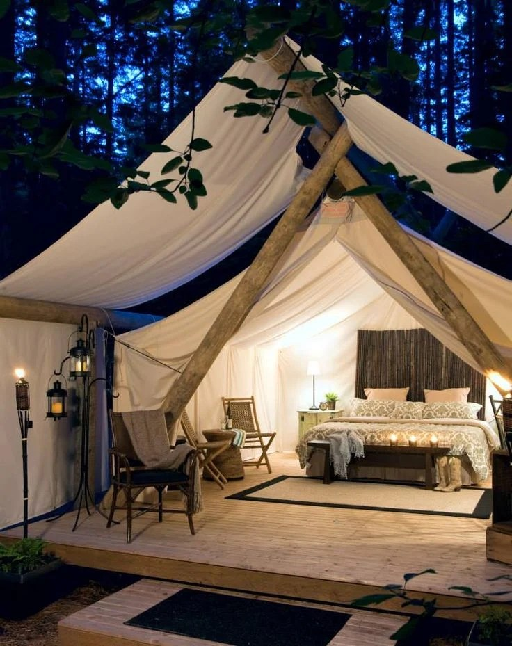 white tent for camping with plywood floor and full bed inside with rustic beams
