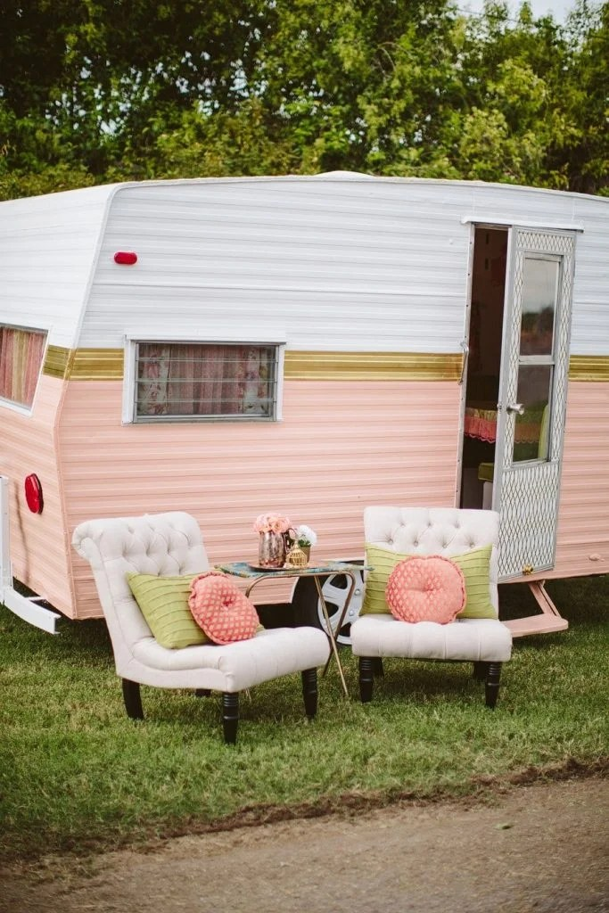 pink and white small camper with white tufted accent chairs outside with throw pillows