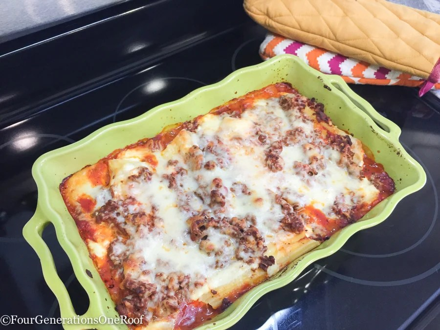 manicotti with hamburger in green casserole dish on stovetop