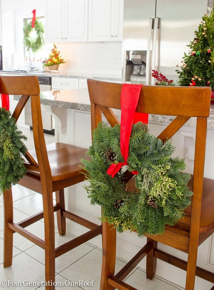 Christmas Kitchen 2016   Featuring hanging wreaths on the barn doors, hanging wreaths on the stools and windows along with a mini boxwood Christmas tree as a centerpiece on the island   Four Generations One Roof