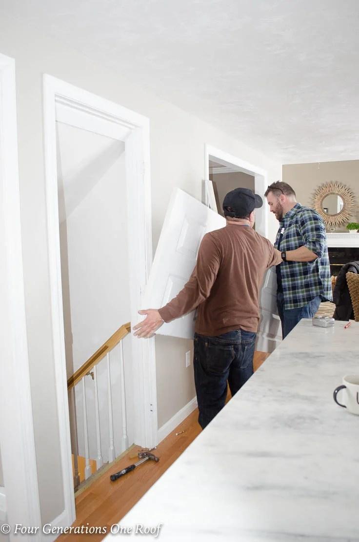 men removing White basement kitchen door Barn Door Installation without Removing Door Trim