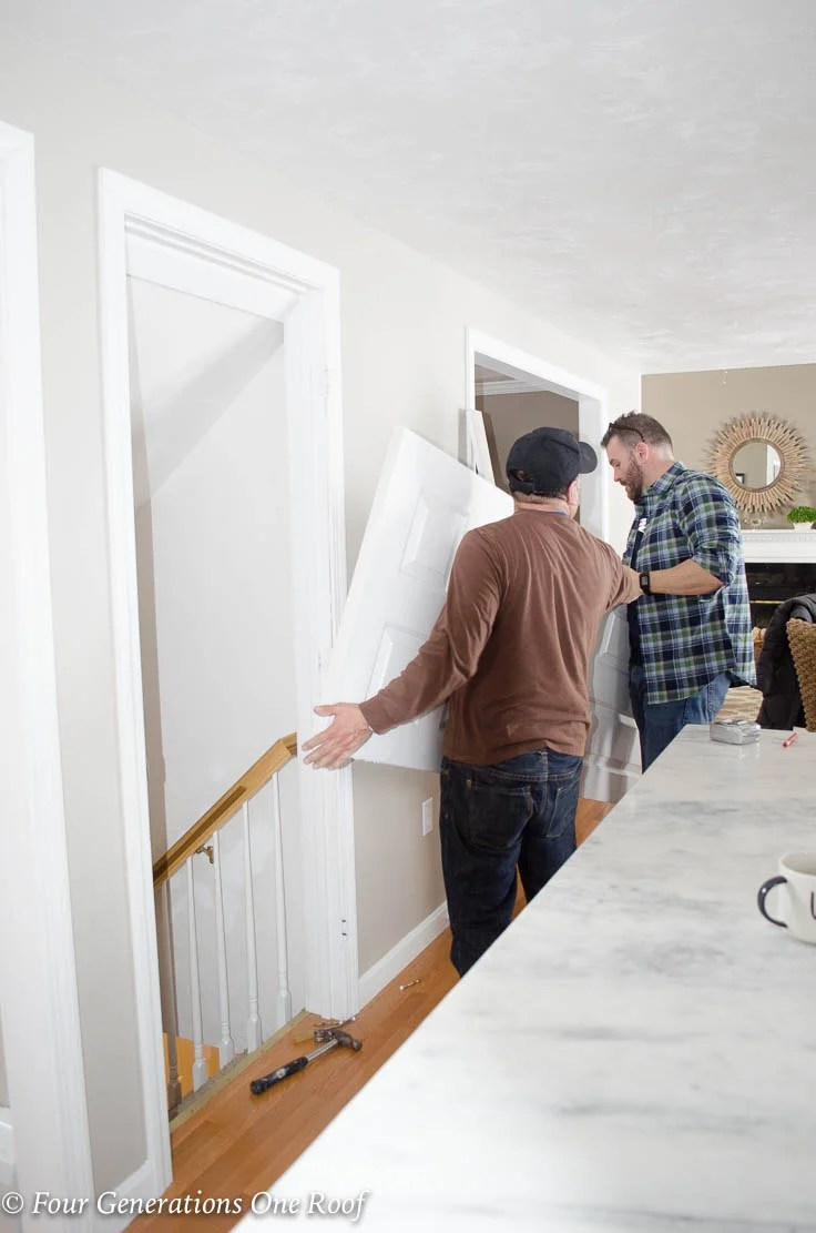 men removing White basement kitchen door Barn Door Installation without Removing Door Trim