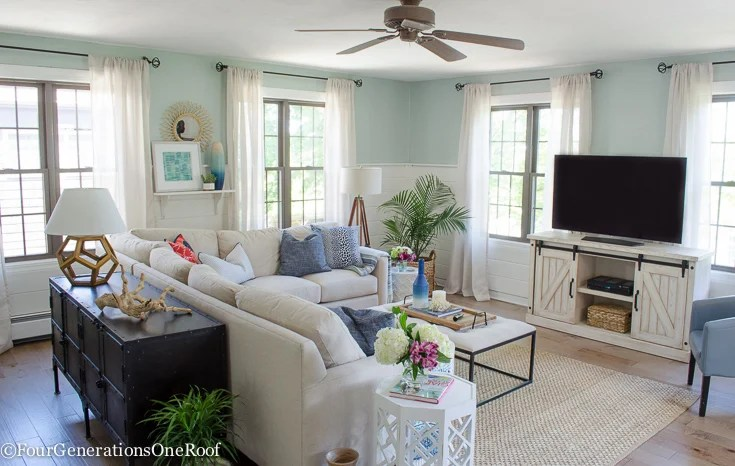 Coastal Style Living Room with Maple Hardwood flooring, white sectional and tweed rug.