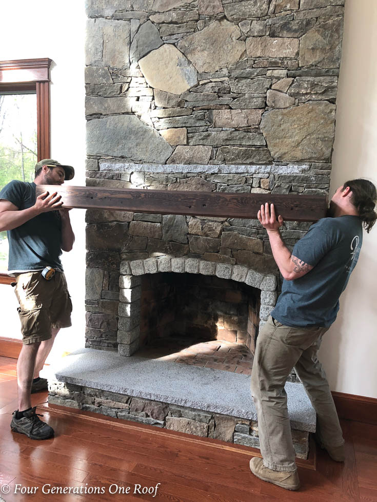 stone fireplace, wood pine beam mantel being installed by two men, cherry floors, stained trim