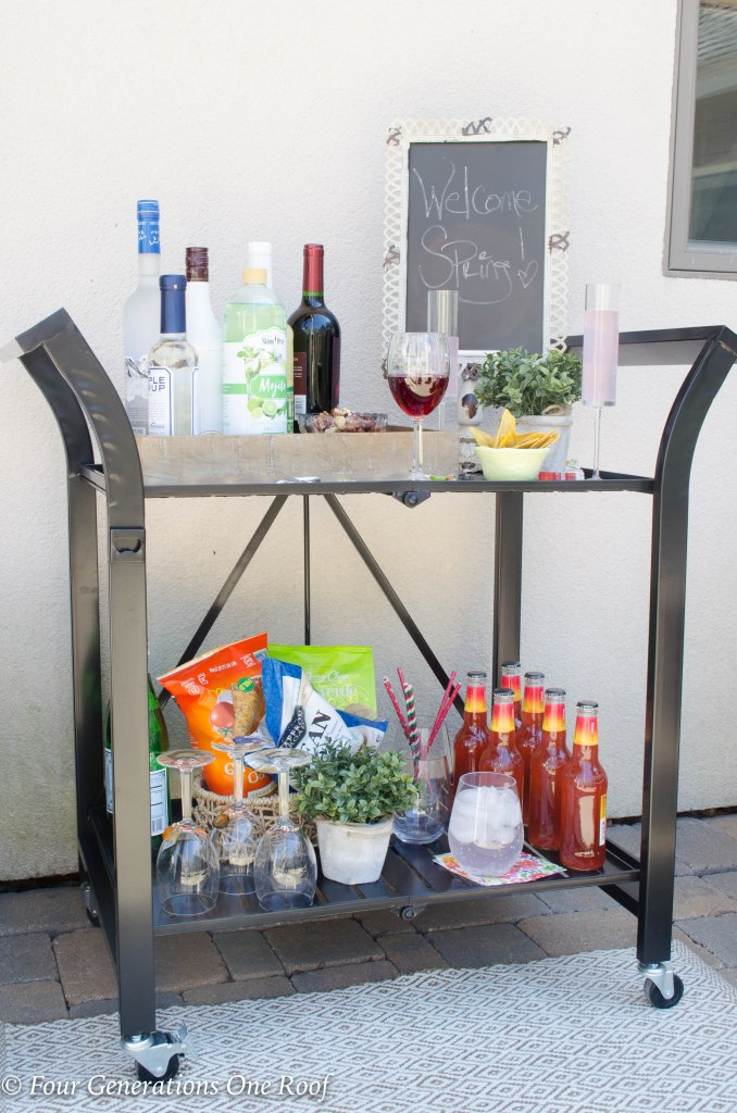 15 minute black metal bar cart setup   wooden tray filled with liquor and mixers   champaign glasses   chalk board sign