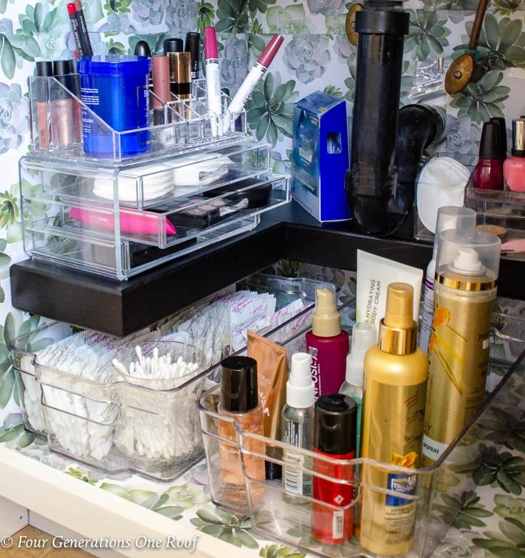 Pretty organized under bathroom sink with black DIY premade shelf + flower wallpaper - drawer liners + acrylic makeup and toiletry organizers