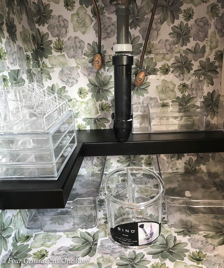 under bathroom sink lined with green flower drawer liner, black premade shelf and acrylic organizers