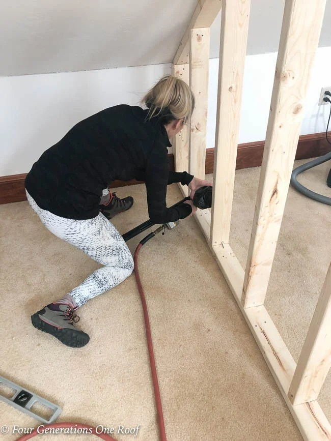 "Jessica Bruno nailing 2x4's every 16"" on center to create a closet wall"