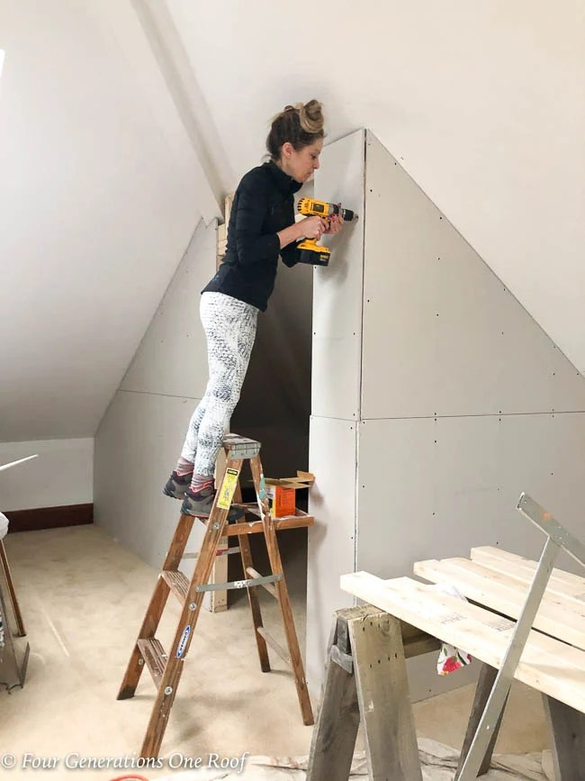 Jessica Bruno screwing drywall to the 2x4 frame closet wall with Dewalt screw gun + wood ladder