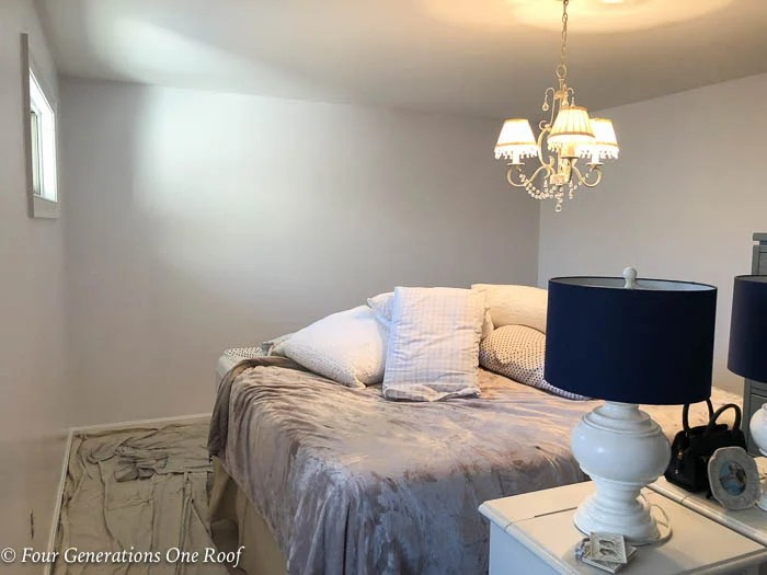white bedroom walls, chandelier, bed in middle of room while painting