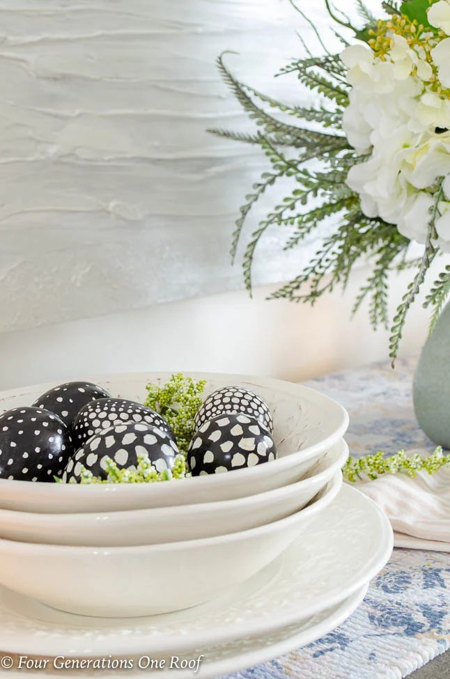 White tuscan bowls with speckled black and white eggs, white modern artwork, flowers