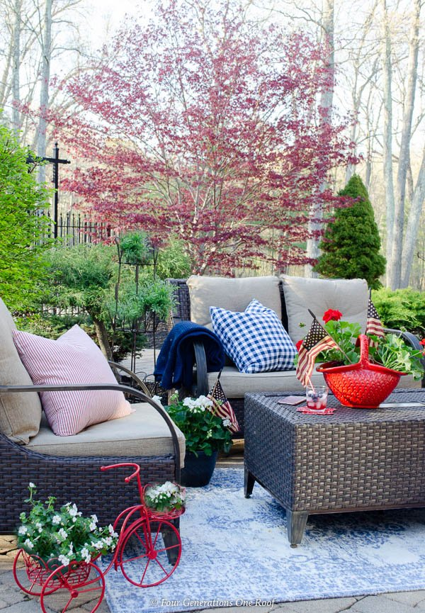 Classy Patriotic Decor Ideas on our Patio brown rattan outdoor furniture, american flag, red geraniums, blue outdoor rug, red and blue outdoor pillows, red planter, red tricycle planter, japanese maple tree, paver patio