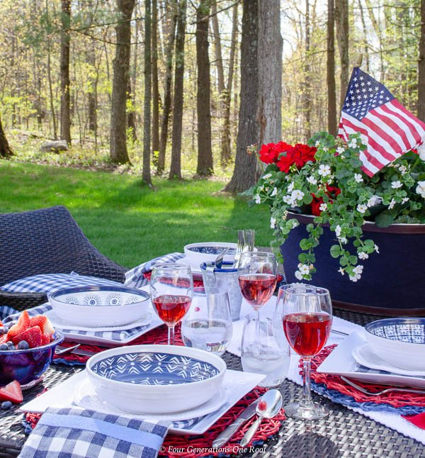 patriotic outdoor table on lawn, ice bucket centerpiece filled with geraniums and flags, red striped tablecloth, melamine blue and white dishes, wine glass filled with red wine